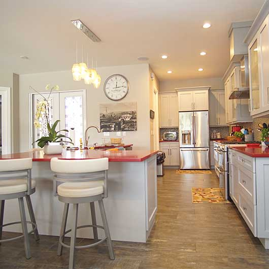 spacious kitchen with hanging lights and red countertops