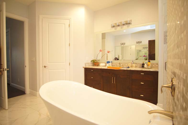White bathtub and brown cabinets in bathroom built by SPEC Development