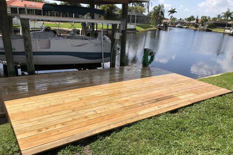 Boat in water in front of boat dock remodeled by SPEC Development