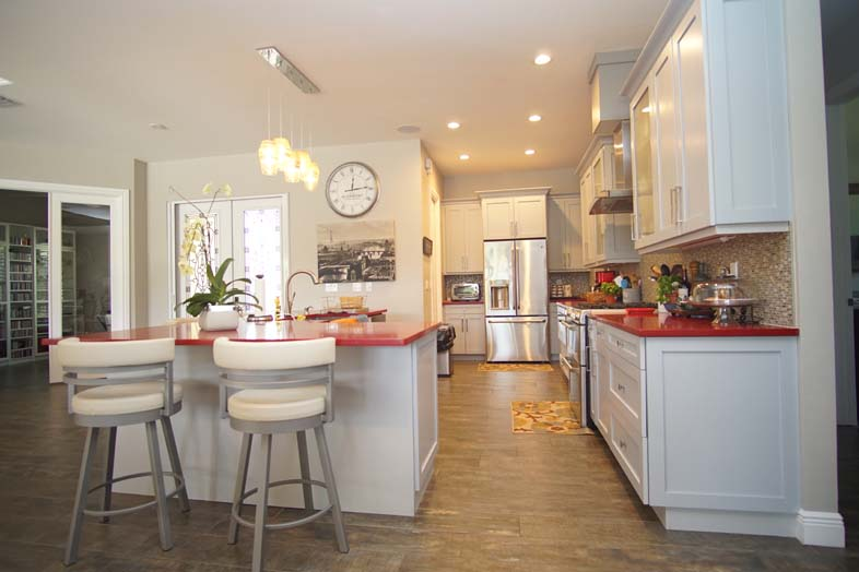 White kitchen cabinets and white barstools, designed by SPEC Development