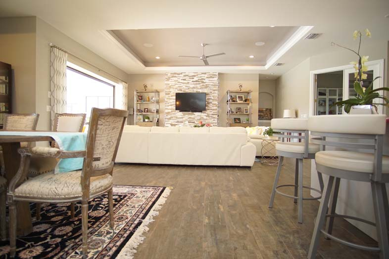 Open floor plan with white couch and mounted TV, designed by SPEC Development